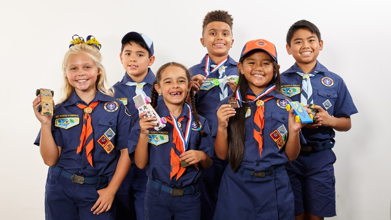 A group of scouts smiles for the camera while showing off their creatively decorated cars.