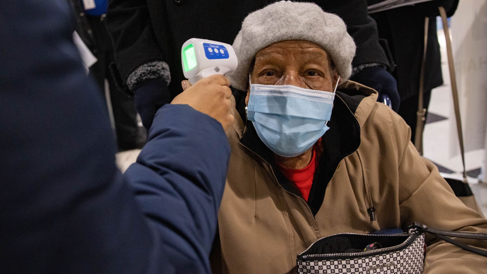 Mae Jackson, 99, has her temperature checked before entering to receive the COVID-19 vaccine at Fair Park in Dallas on Thursday, Jan. 14, 2021.
