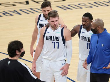 Dallas Mavericks guard Luka Doncic (77) talks with assistant coach Jamahl Mosley and teammates during the second half against the New York Knicks in an NBA basketball game Friday, April 2, 2021, in New York.