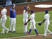 Rangers second baseman Rougned Odor (12) celebrates with manager Chris Woodward (8, center) after a win against the Rockies on Friday, July 24, 2020, at Globe Life Field in Arlington.