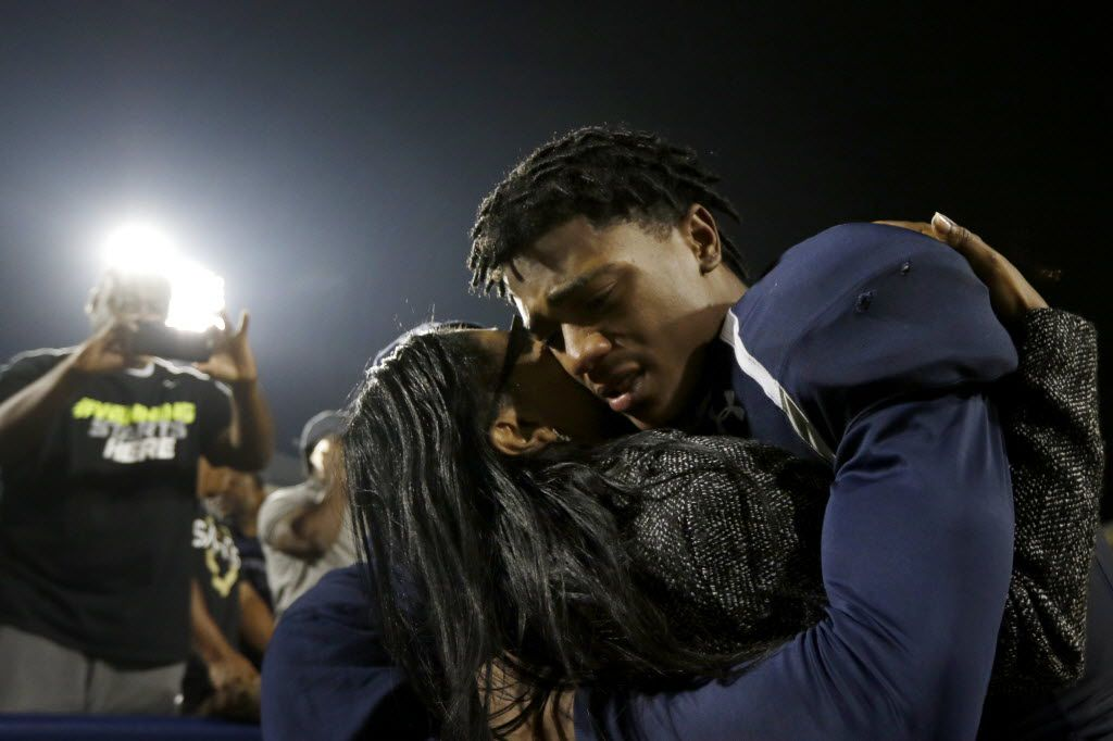 From left, Nicole Miller hugs her son Frisco Lone Star Rangers Chris Miller after the Frisco Lone Star Rangers win against the Lake Dallas Falcons at Eagle Stadium in Allen on Friday, Dec. 11, 2015. (Rachel Woolf/The Dallas Morning News)