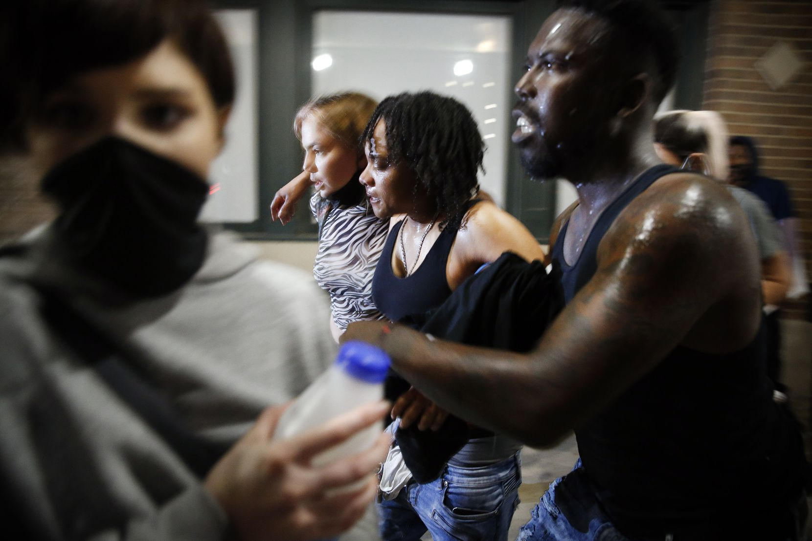 A female protestor (center) is helped to her feet after she was hit by a projectile as they were confronted by Dallas Police tactical officers at Wood St. and S. Lamar St. in downtown Dallas, Friday, May 29 2020. People were marching in protest of the in-custody death of George Floyd when they confronted Dallas Police tactical officers and tear gas was fired.