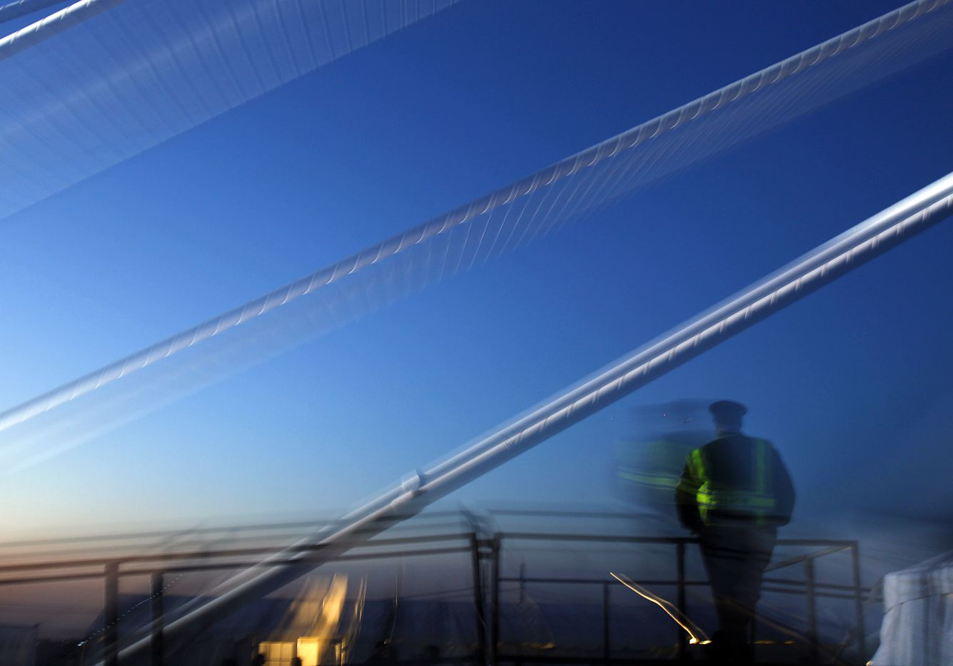The high tension cables of  the Margaret Hunt Hill Bridge are a blur in this image as a Dallas police officer patrols the bridge before  opening-night festivities in Dallas, March 2, 2012. (Tom Fox/The Dallas Morning News)