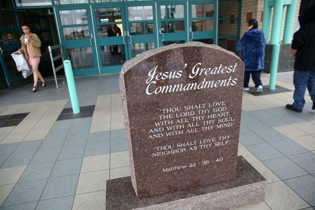 Shoppers walk by a monument with two of the Ten Commandments at an entrance to Music City Mall in Lewisville on Dec. 29, 2017. The Ten Commandments will be featured year-round in the lower level of the mall, while a second stone tablet with two commandments will be displayed on an upper level.