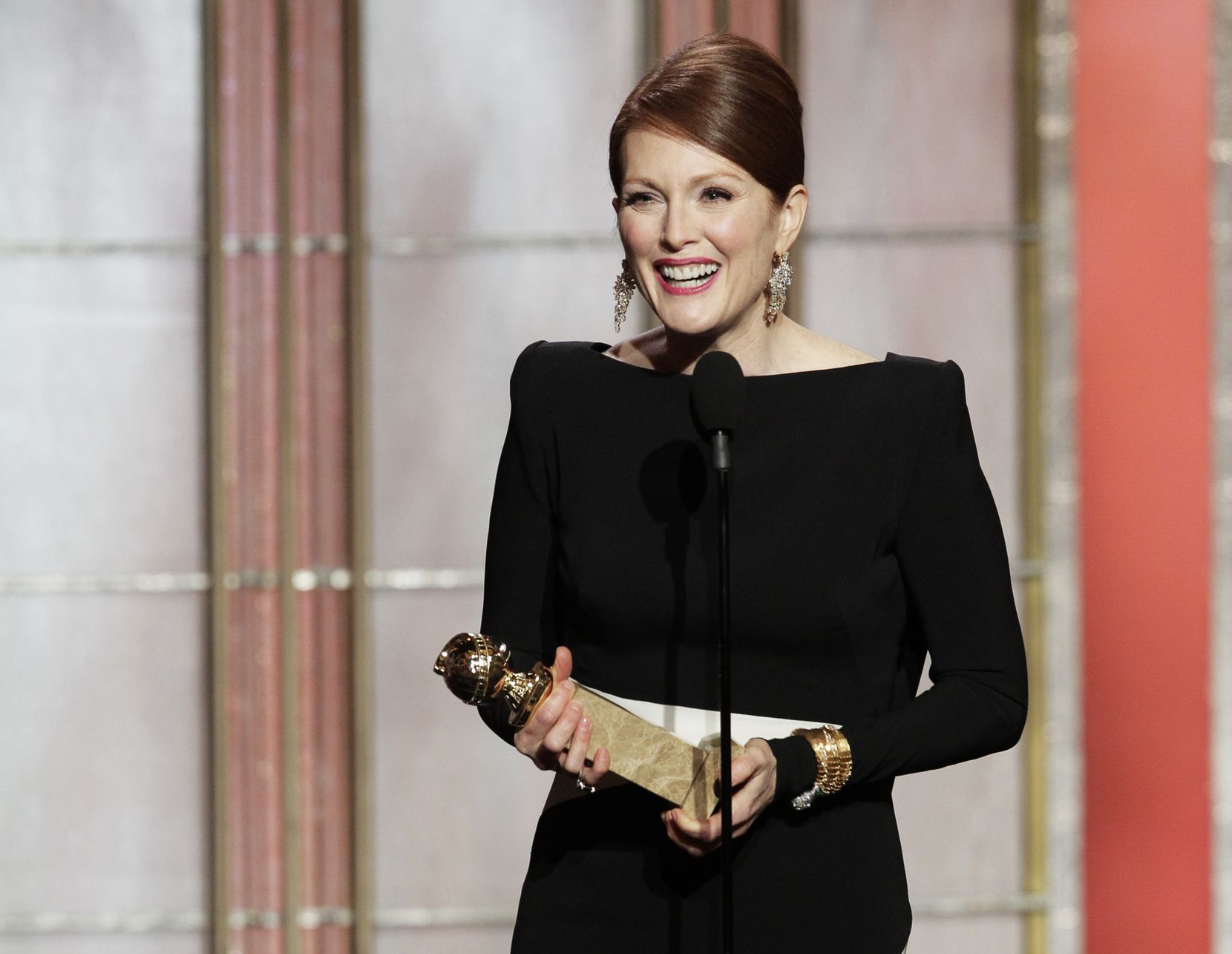 "In this Jan. 13, 2013 photo, Julianne Moore, winner of the award for best actress in a mini-series or TV movie for her role in ""Game Change,"" appears on stage during the 70th Annual Golden Globe Awards at the Beverly Hilton Hotel in Beverly Hills, Calif."