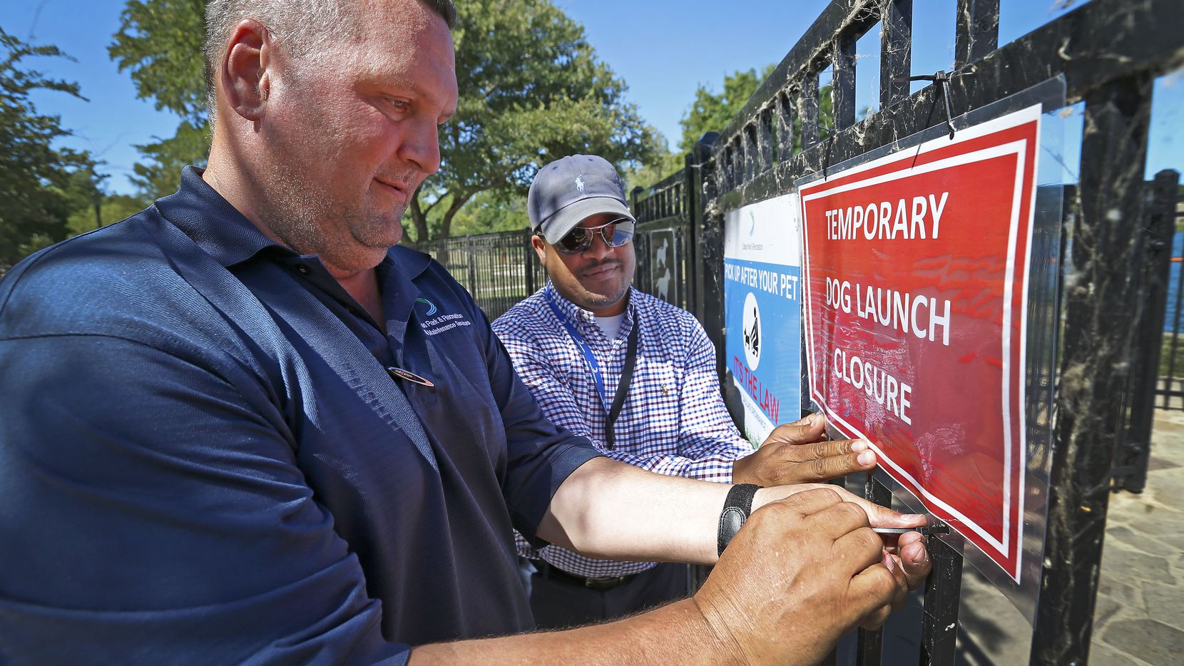 Russell Hooper, left, and Will Stonum of the Dallas Parks & Recreation, put up a closure sign on the gate of the dog launch at White Rock Lake on Thursday.