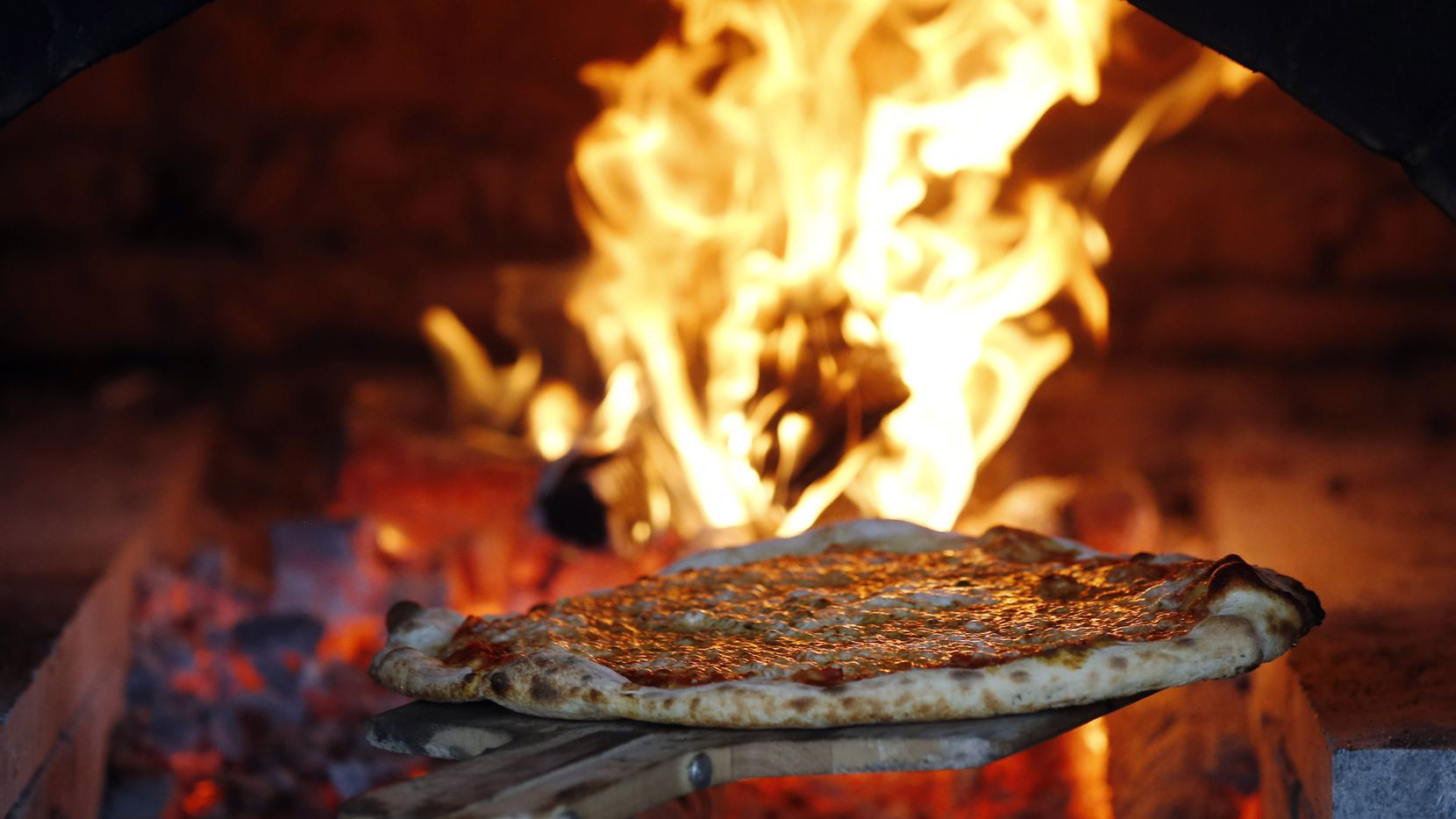 Cheese pizza is pulled from the wood fired oven at Flatbread Company in Dallas. The restaurant is expected to open Jan. 16, 2020.
