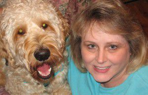 Teri Holamon and her Goldendoodle Gibbs enjoy reading together. (Photo submitted by Teri Holamon)