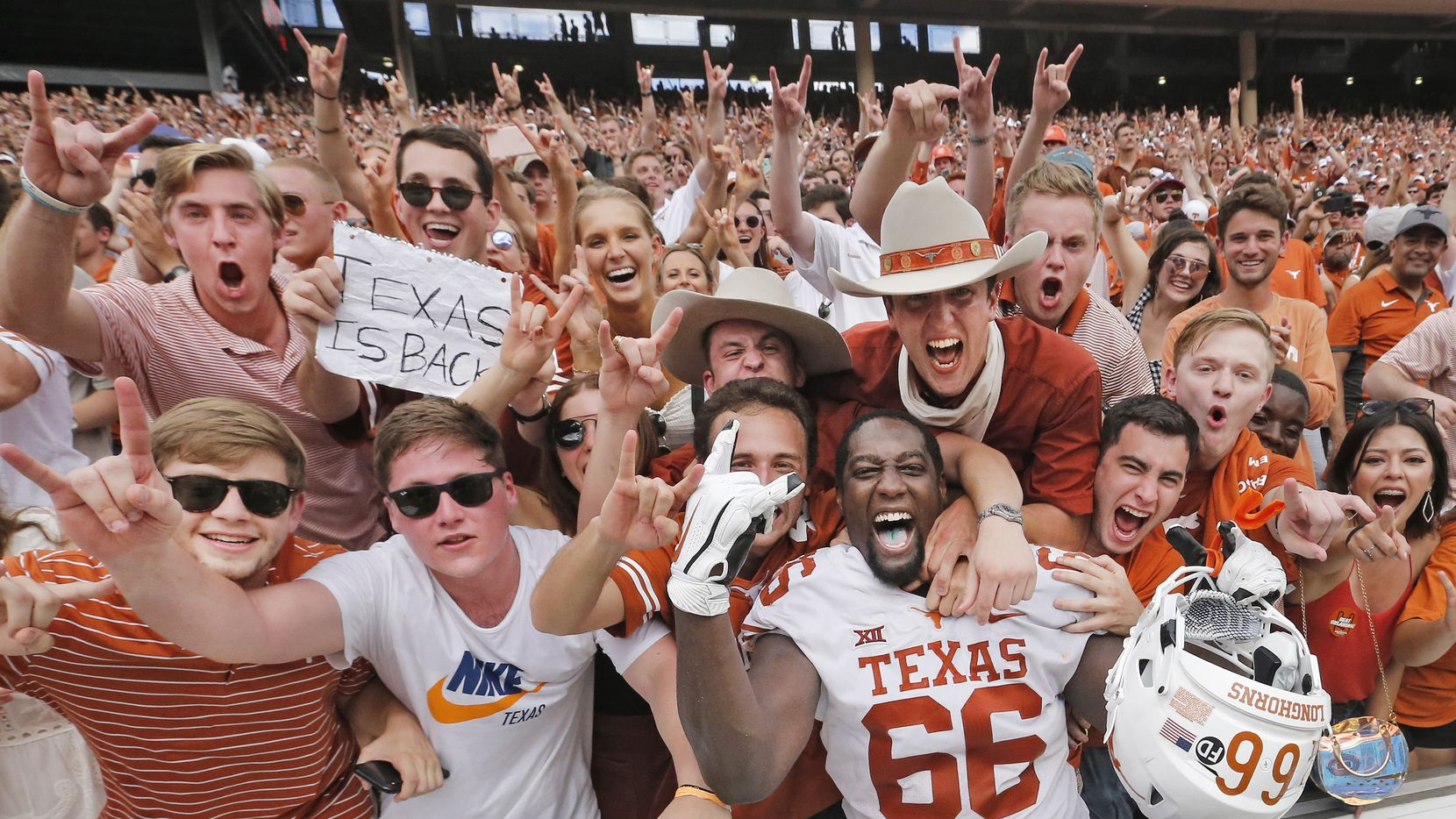 Texas Longhorns offensive lineman Calvin Anderson (66) celebrates with fans after the Longhorns 48-45 win during the University of Texas Longhorns vs. the Oklahoma Sooners NCAA football game at the Cotton Bowl in Dallas on Oct. 6, 2018. (Louis DeLuca/The Dallas Morning News)