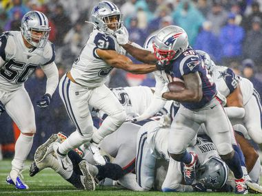 FILE - Patriots running back Sony Michel (26) attempts to power past Cowboys cornerback Byron Jones (31) during the second half of a game at Gillette Stadium in Foxborough, Mass., on Sunday, Nov. 24, 2019.