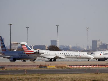 American Eagle and American Airlines planes make their way toward the runway before taking off at DFW International Airport.