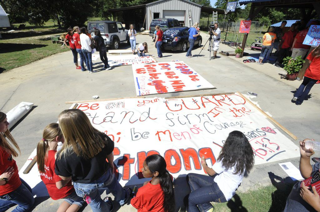Kountze cheerleaders, friends and supportive parents who are standing up for their kids and their beliefs, were making large signs and painting car windows Wednesday afternoon that will be seen around Kountze in support of the cheerleaders who were told they could not put scripture on their football signs. Each game this season, the Kountze cheerleadershave made Christian-themed run-through signs for the football players. The signs, which featured scripture verses, went viral and have now been stopped by the school district's leaders who were told by a group the signs were offensive and against the separation of church and state. Dave Ryan/The Enterprise