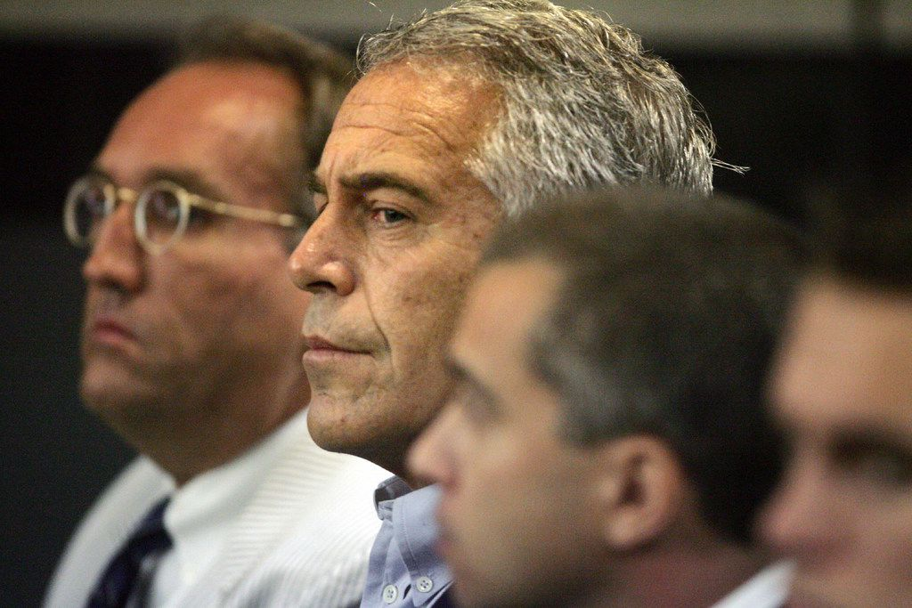 FILE - In this July 30, 2008, file photo, Jeffrey Epstein, center, appears in court in West Palm Beach, Fla. Over the last decade he sought to portray himself as a generous benefactor to children, giving to organizations including a youth orchestra, a baseball league and a private girls' school a few blocks from his Manhattan mansion. But Epstein's guilty plea in 2008 for soliciting a minor for prostitution has not made that easy. On July 8, 2019, Epstein pleaded not guilty in federal court in New York to sex trafficking charges. (Uma Sanghvi/Palm Beach Post via AP, File)