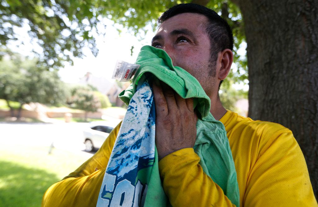 Muriel Lopez wipes his face of sweat during a break from roofing a house in Arlington, Texas on July 19, 2018.  (Nathan Hunsinger/The Dallas Morning News)