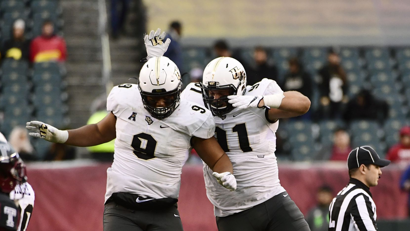 PHILADELPHIA, PA - NOVEMBER 18: Trysten Hill #9 of the UCF Knights and teammate Joey Connors #91 air bump after a stop against the Temple Owls during the third quarter at Lincoln Financial Field on November 18, 2017 in Philadelphia, Pennsylvania. UCF defeated Temple 45-19. (Photo by Corey Perrine/Getty Images)
