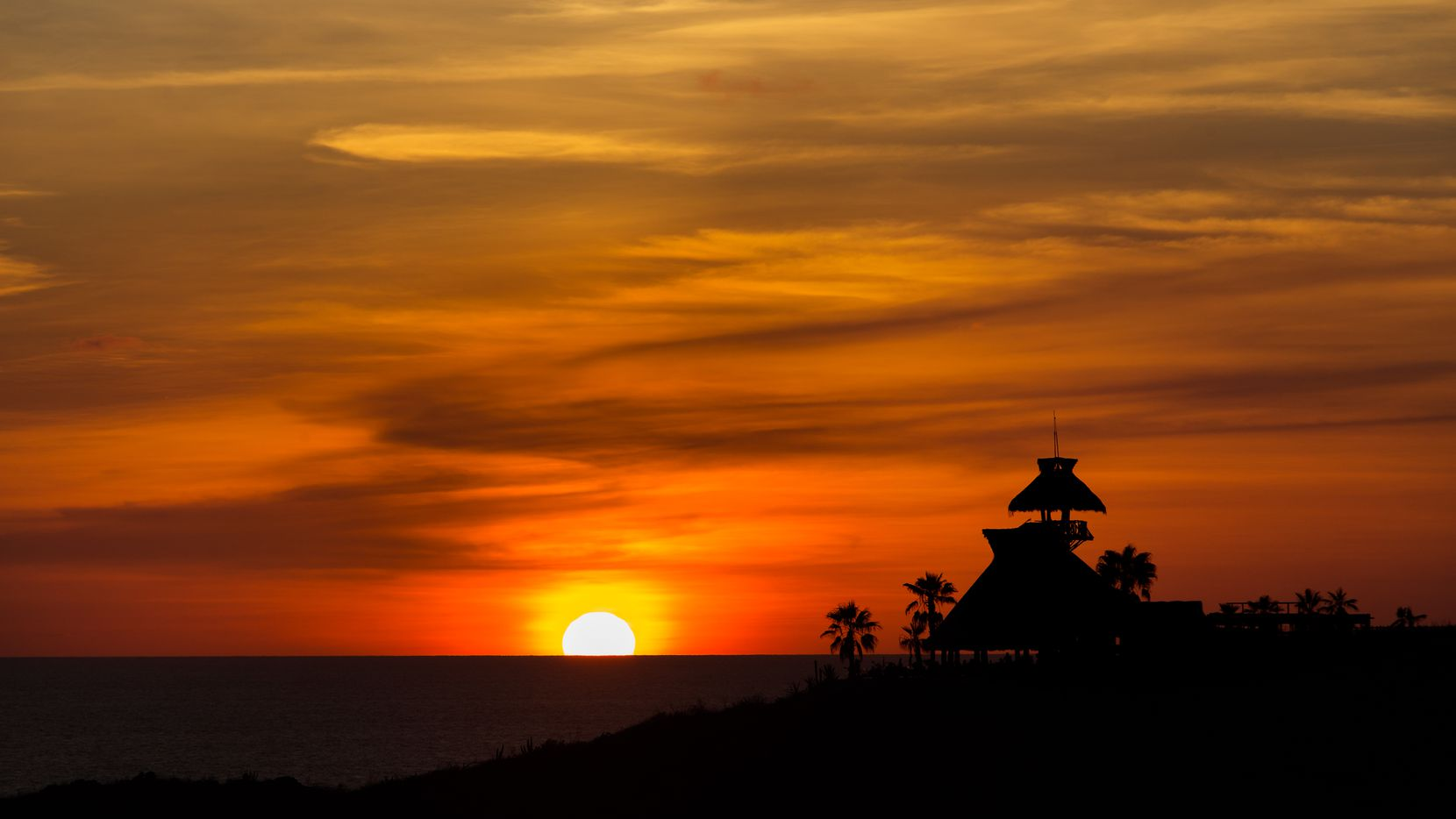 The sun sets behind the oceanfront El Mirador restaurant in Todos Santos, Mexico.