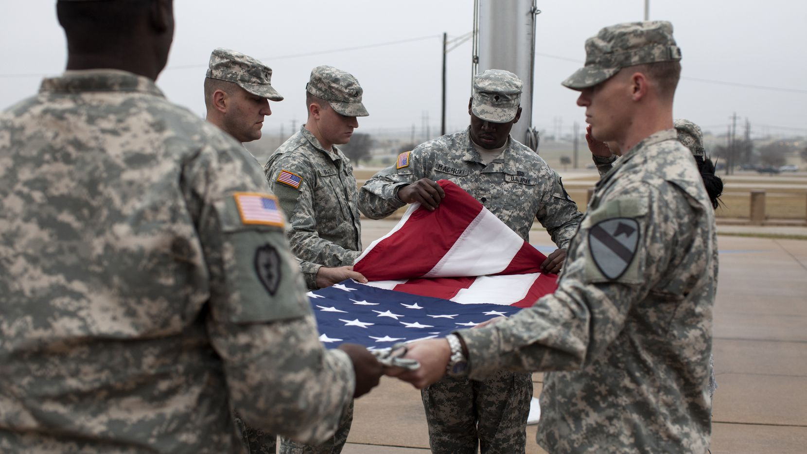 Soldiers fold a lowered flag at Fort Hood on Dec. 30 to mark the official end of the war in Afghanistan.
