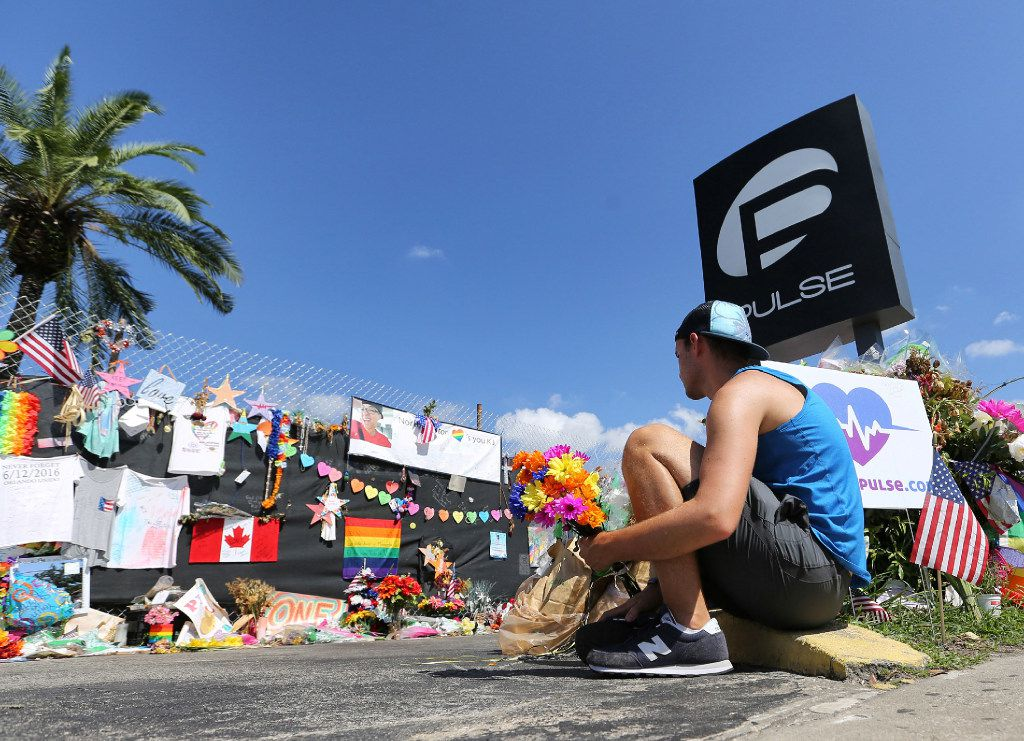 On the eve of the one-month anniversary of the Pulse nightclub massacre, a friend of two of the victims places flowers as visitors continue to flock to the club to their pay their respects on Monday, July 11, 2016 in Orlando, Fla. Today, family members of those who died will tell an Orlando judge what they want done with the recordings of 911 calls from that night.  (Joe Burbank/Orlando Sentinel/TNS)