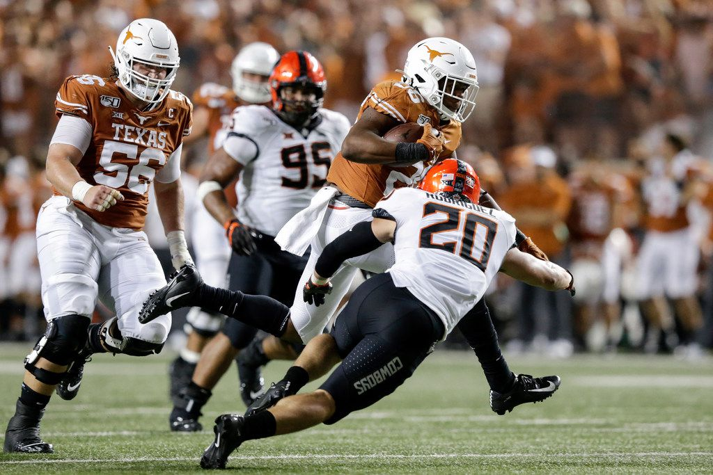 Keaontay Ingram #26 of the Texas Longhorns runs the ball in the fourth quarter defended by Malcolm Rodriguez #20 of the Oklahoma State Cowboys at Darrell K Royal-Texas Memorial Stadium on September 21, 2019 in Austin, Texas.