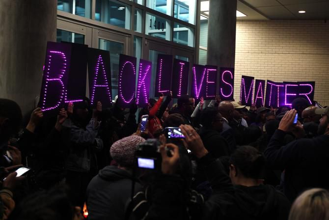 """Protesters held up letters that spelled out """"Black Lives Matter"""" at a protest outside Dallas police headquarters in the aftermath of the police shooting of a black man in Ferguson, Mo."""
