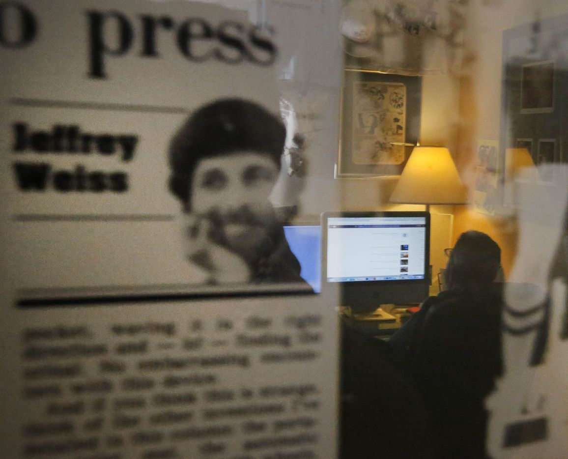 Jeffrey Weiss works in his office at his home in Dallas, as seen in a reflection of a framed press clipping on the wall in February 2017.