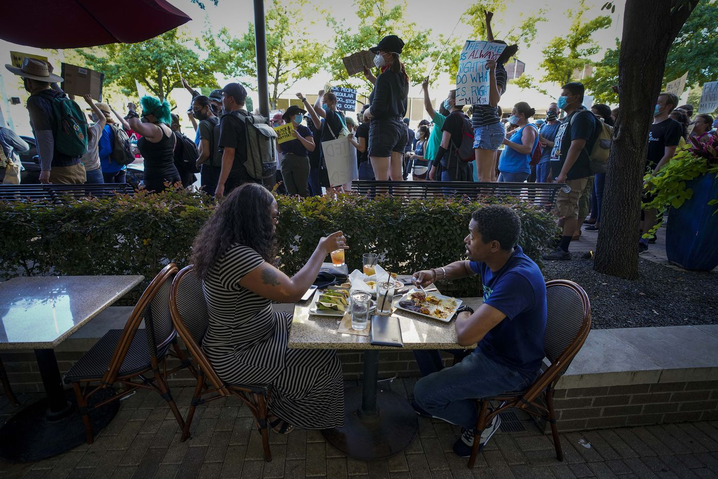 A couple eats dinner at Gloria's Latin Cuisine at the corner of Lemmon Avenue and Carlisle Street as a protest that began at Cole Park pauses while marching around the West Village and Uptown neighborhoods on Friday, June 5, 2020, in Dallas. Protests continued Friday in the response to the death of George Floyd.