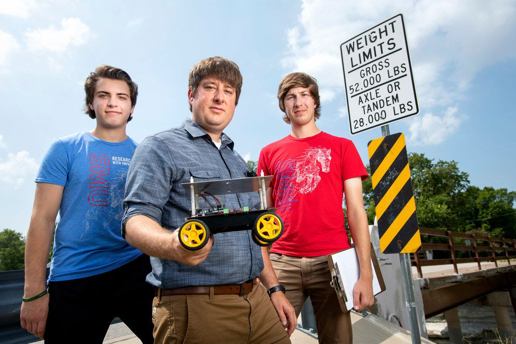 SMU assistant professor of civil and environmental engineering Brett Story, center, poses for a portrait with undergraduate researcher Chris Stenzel, left, and research assistant Jase Sitton, right, at a bridge they are monitoring in Garland. Story and his team use accelerometer data collected from smart phones passing over a bridge to detect changes in the bridge's vibration frequency which evidence changes in structural integrity.