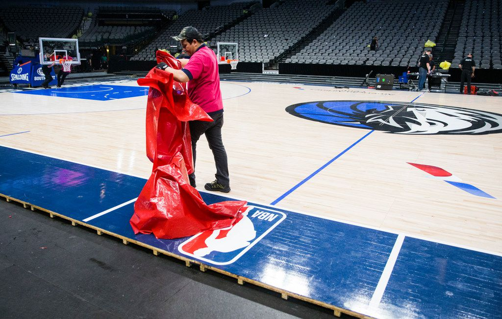 Crews break down the court after the Dallas Mavericks beat the Denver Nuggets 113-97 on Wednesday, March 11, 2020 at American Airlines Center in Dallas. During the game, the NBA suspended all games due to the spread of the new coronavirus. (Ashley Landis/The Dallas Morning News)