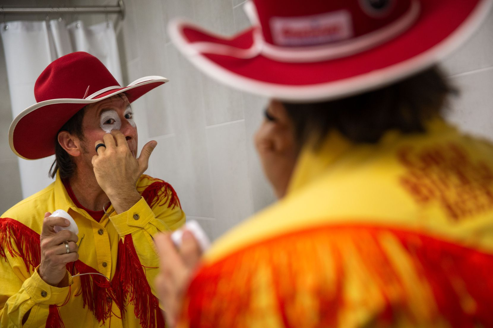"Barrel man John Harrison gets dressed during the sixth night of the National Finals Rodeo at Globe Life Field in Arlington, Texas, on Tuesday, Dec. 10, 2020. Harrison, whose grandfather was a bull rider, has been a barrel man since 2002. ""Being a rodeo clown, we're probably the only men out there who fight their wives over eyeliner,"" Harrison said. (Lynda M. González/The Dallas Morning News)"
