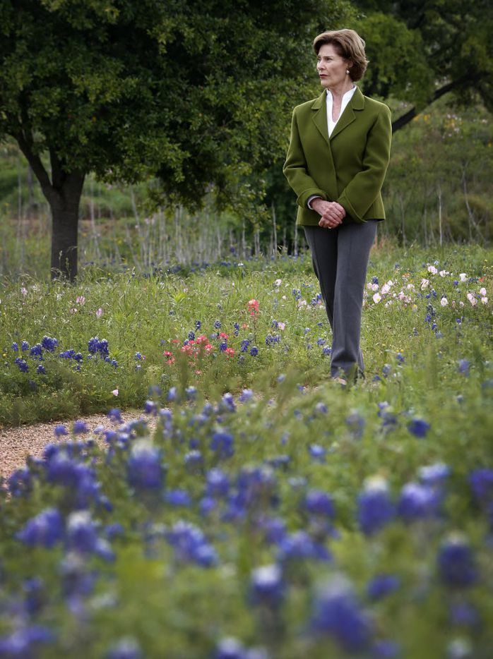 Former first lady Laura Bush walks by bluebonnets during a tour of the Native Texas Park at the Bush Center on the SMU campus in Dallas on April 13, 2016.