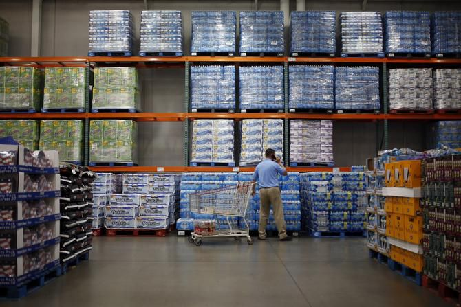 A customer shops for bottled water at a Costco store in Louisville, Ky. Warehouse clubs' per-unit prices are good, but some items aren't as good a value — the paper products to the left, for example, might be a better deal at the grocery store on sale.