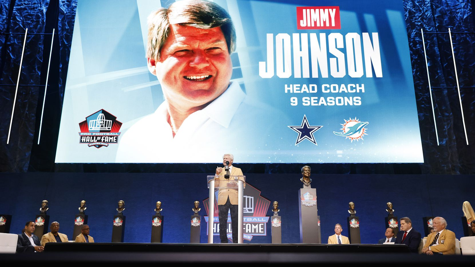 Pro Football Hall of Fame inductee Jimmy Johnson of the Dallas Cowboys (left) delivers his speech during the Centennial Class of 2020 enshrinement ceremony at Tom Benson Hall of Fame Stadium in Canton, Ohio, Saturday, August 7, 2021.