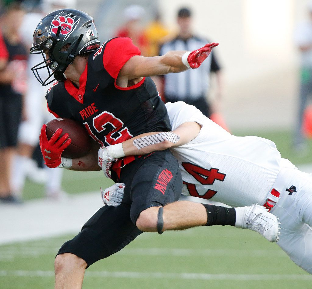 Colleyville Heritage High School quarterback Brayden Gerlich (12) is tackled by Lovejoy High School strong safety Trent Rucker (24) during the first half as Colleyville Heritage High School hosted Lovejoy High School as part of the Tom Landry Classic at Eagle Stadium in Allen on Saturday, August 31, 2019. (Stewart F. House/Special Contributor)
