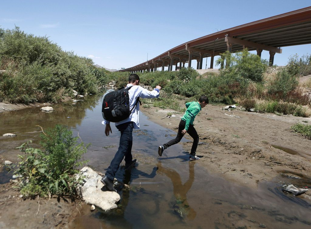 In this June 7, 2019 photo, people cross the Rio Grande into the United States to turn themselves over to authorities and ask for asylum, as seen from Ciudad Juarez, Chihuahua, Mexico, opposite El Paso