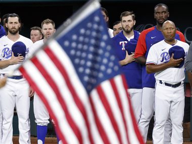 Texas Rangers players and coaches stand for the national anthem during the Texas Rangers Baseball Hall of Fame induction ceremony at Globe Life Field in Arlington, Saturday, August 14, 2021.