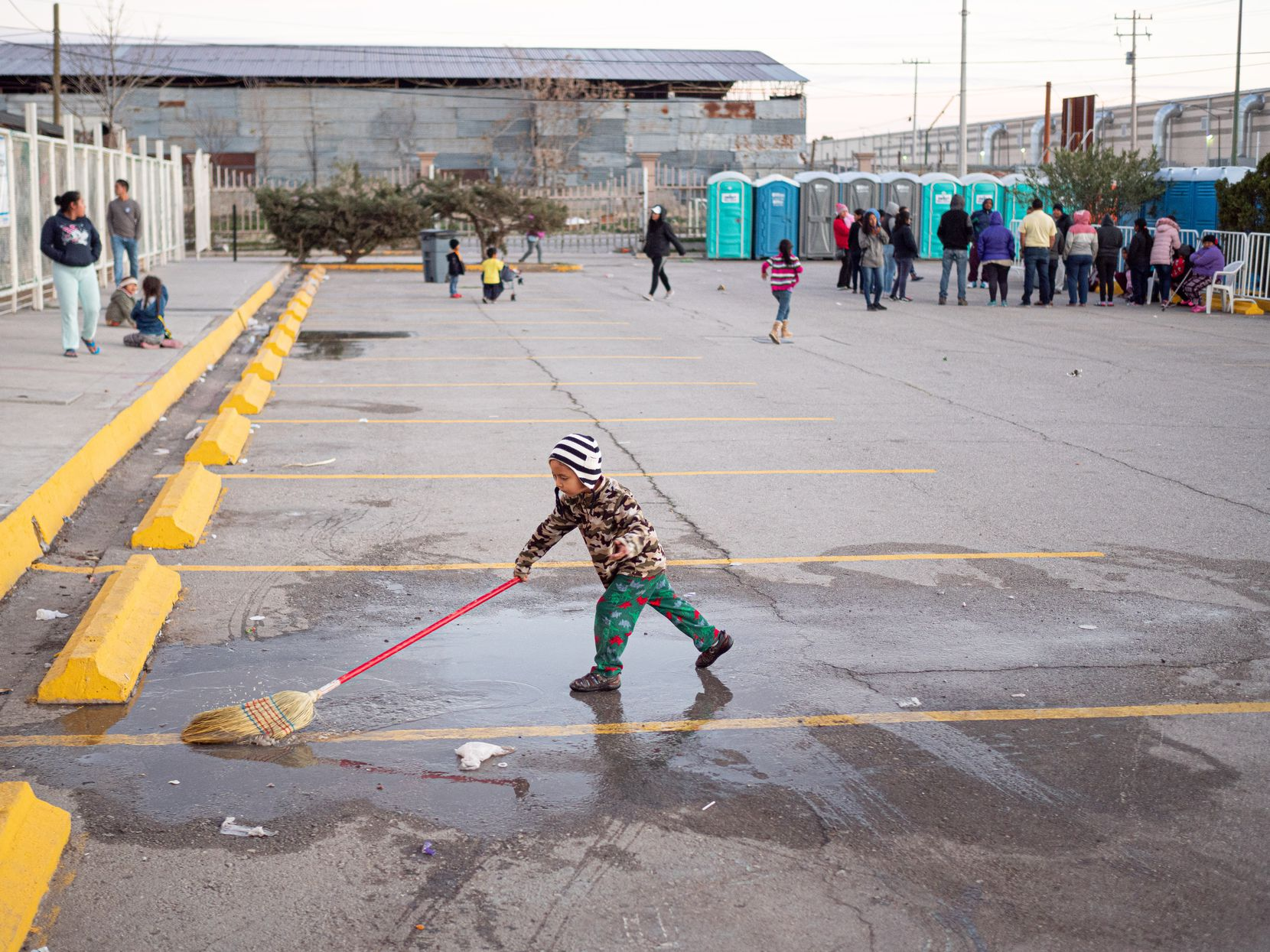 A young migrant plays with a broom in a puddle at the state run migrant shelter in Juarez.