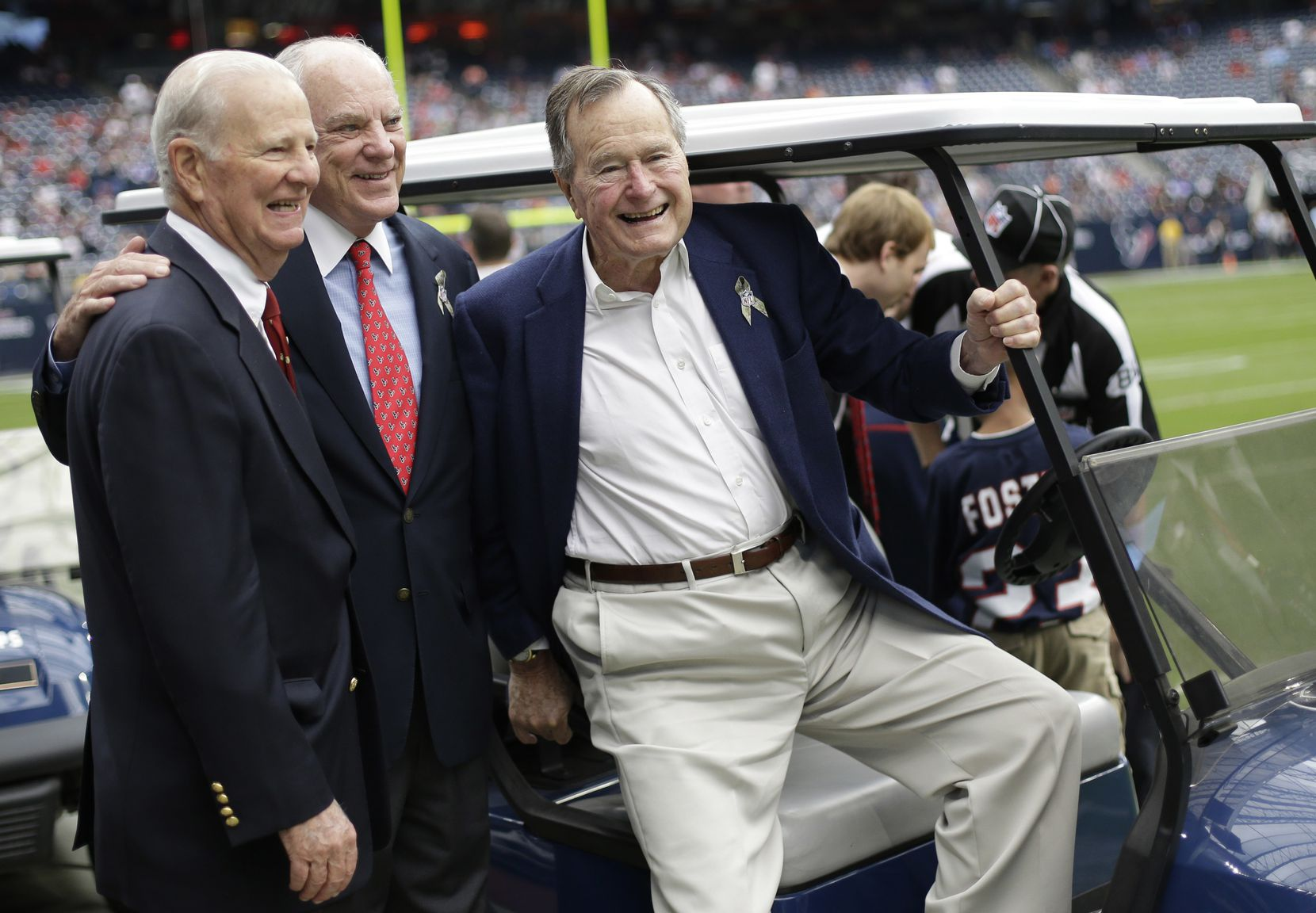 Former President George H.W. Bush (right) shown in a 2012 sideline appearance at a Houston Texans game with his close partner in politics, former Secretary of State James Baker (left), and team owner Bob McNair, was an indefatigable booster of the Republican brand in a state dominated by Democrats when he moved to Texas after World War II.