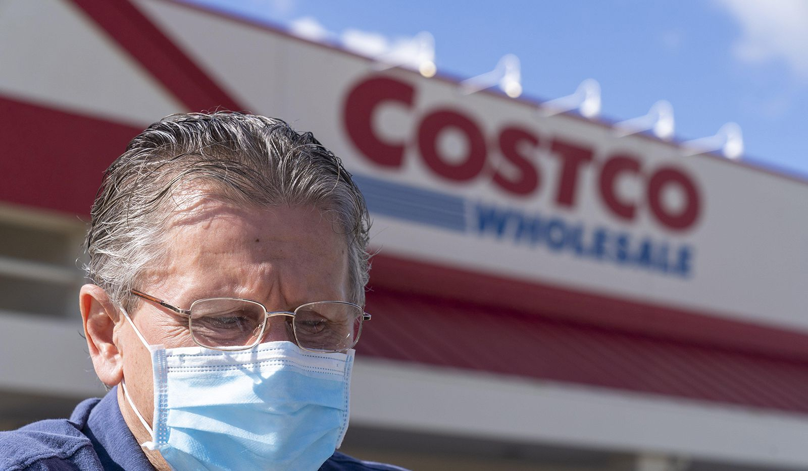 Dobro Hajek, of Jupiter, wears a masks as he pushes his grocery cart to his car at a Costco store in Palm Beach Gardens.