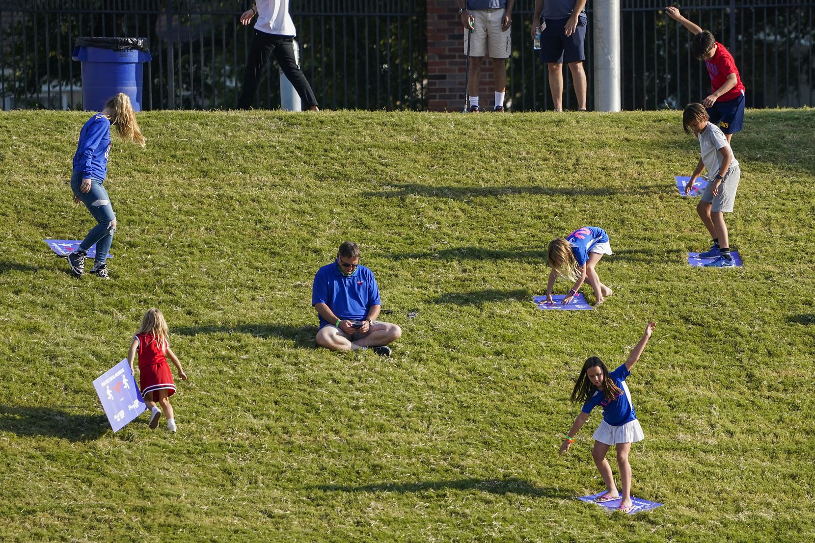 Children use social distancing signs to slide down the hill in the south end zone during the second half of an NCAA football game between SMU and Memphis at Ford Stadium on Saturday, Oct. 3, 2020, in Dallas. (Smiley N. Pool/The Dallas Morning News)