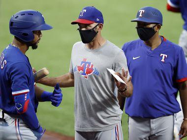 El manager de los Texas Rangers, Chris Woodward (en medio ), utiliza un cubrebocas para dar indicaciones a su jugador Leody Taveras, el lunes 9 de julio en una práctica realizada en el Globe Life Field de Arlington.