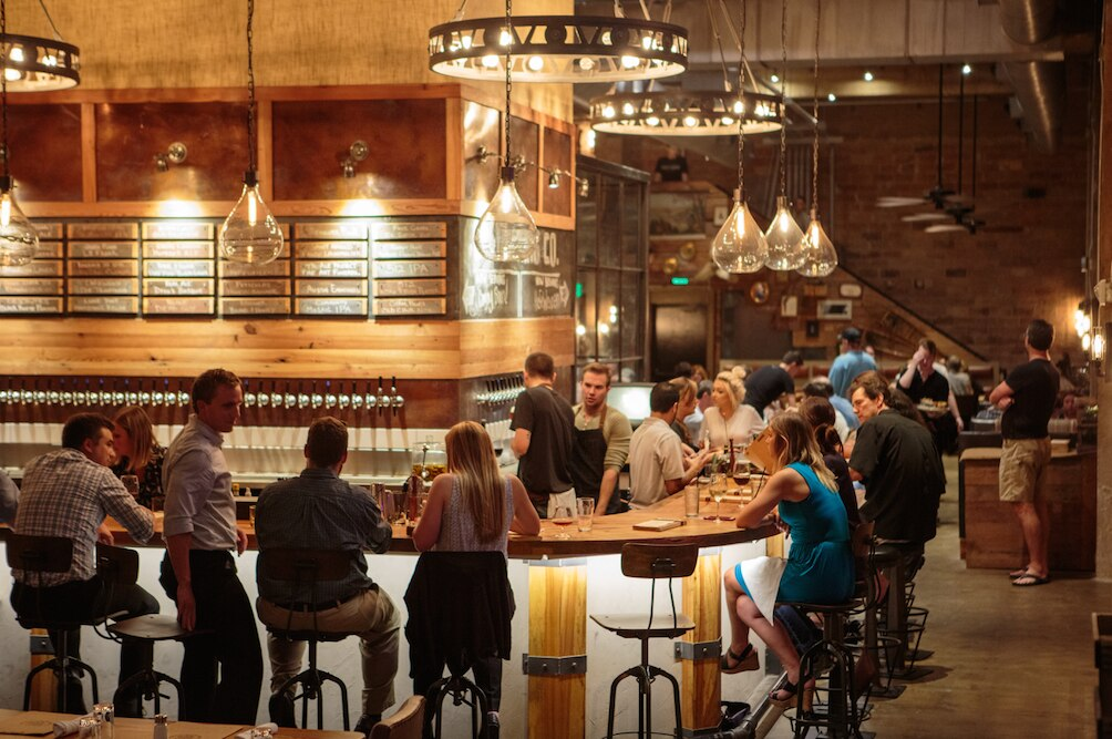 Patrons relax and chat at the Barley and Board bar, which separates the front and back dining areas, on Tuesday, August 11, 2015 in Denton, Texas. The brewpub plans on has 36 beers on tap.