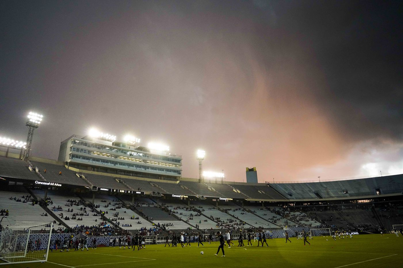 Players head for the locker room as storm clouds roll over the stadium before a CONCACAF Gold Cup Group A soccer match at the Cotton Bowl on Wednesday, July 14, 2021, in Dallas. The start of the game was delayed due to weather.