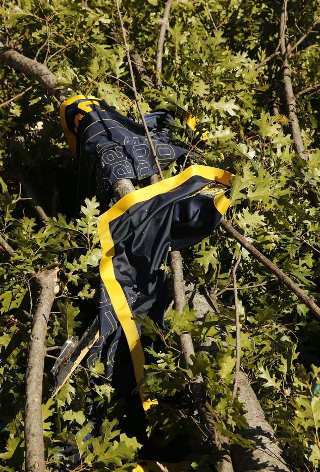 The sports banner from the gymnasium at St. Mark's School of Texas lies among downed trees following the tornado in Dallas, Monday, October 21, 2019. A tornado tore through the entire neighborhood knocking down trees and ripping roofs from homes. (Tom Fox/The Dallas Morning News)