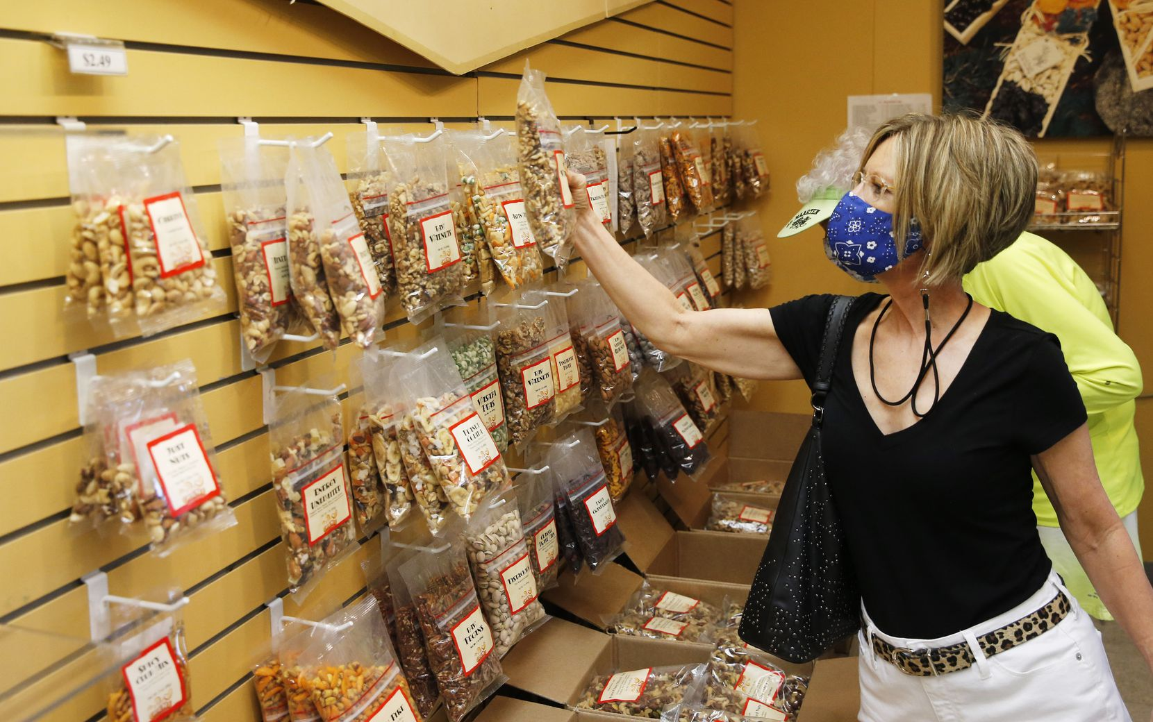 Meredith Clanton of Waxahachie grabbed a bag of walnuts while shopping with family at GNS Foods in Arlington on Tuesday.