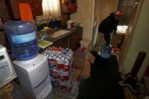 """Resident Demetrius """"People"""" Blair carries a 5-gallon water bottle that the county and a church group provided at his home in Sandbranch, Texas, Thursday, March 10, 2016. (Jae S. Lee/The Dallas Morning News)"""