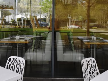 Chairs are stacked on top of tables as restaurant Savor in Klyde Warren Park.