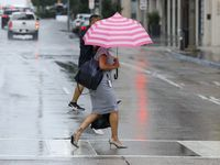 A pedestrian avoids the rain with an umbrella during a thunderstorm in downtown on Tuesday, Aug. 17, 2021, in Dallas. (Elias Valverde II/The Dallas Morning News)