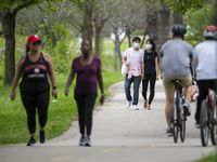 Will Kwon (center left) and Eunsol Noh wear masks as they walk at White Rock Lake on March 29, 2020 in Dallas.