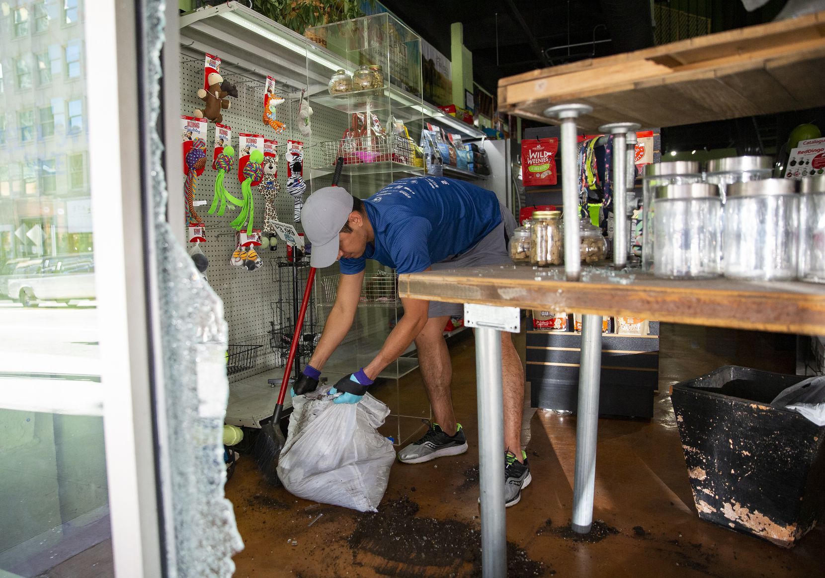 Downtown Pawz co-owner Jonathan Bustos cleans up inside the shop after being hit during last night's protest last night on Saturday morning, May 30, 2020 in Downtown Dallas. Bustos said he learned about the damage after seeing a client's comment on their Facebook.
