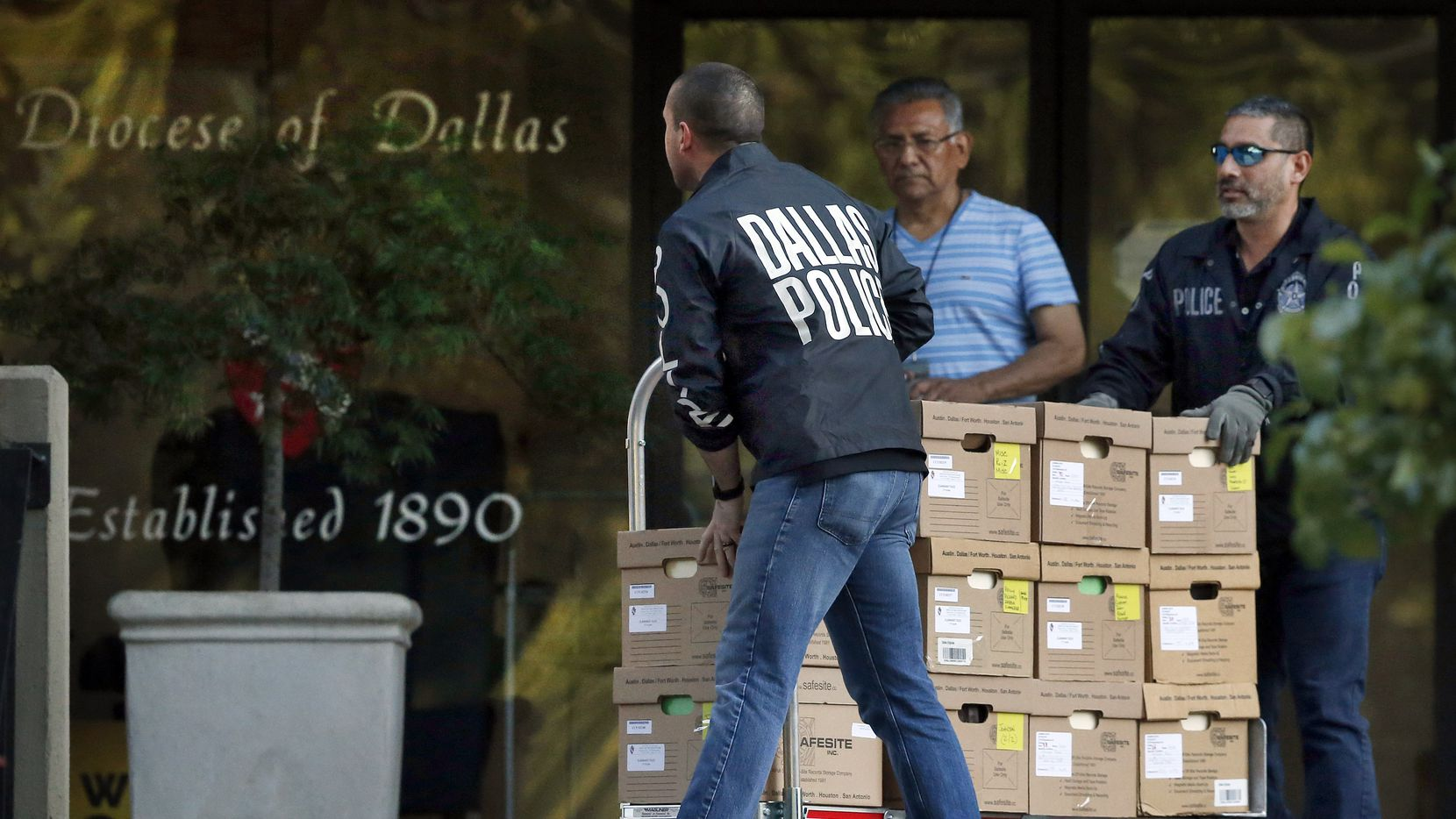 Dallas police officials carted out boxes during a raid on the Catholic Diocese of Dallas on May 15, 2019.
